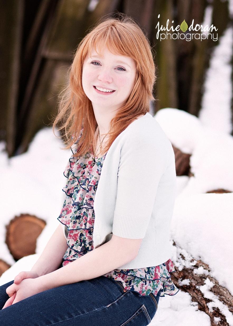 girl sitting on snowy log