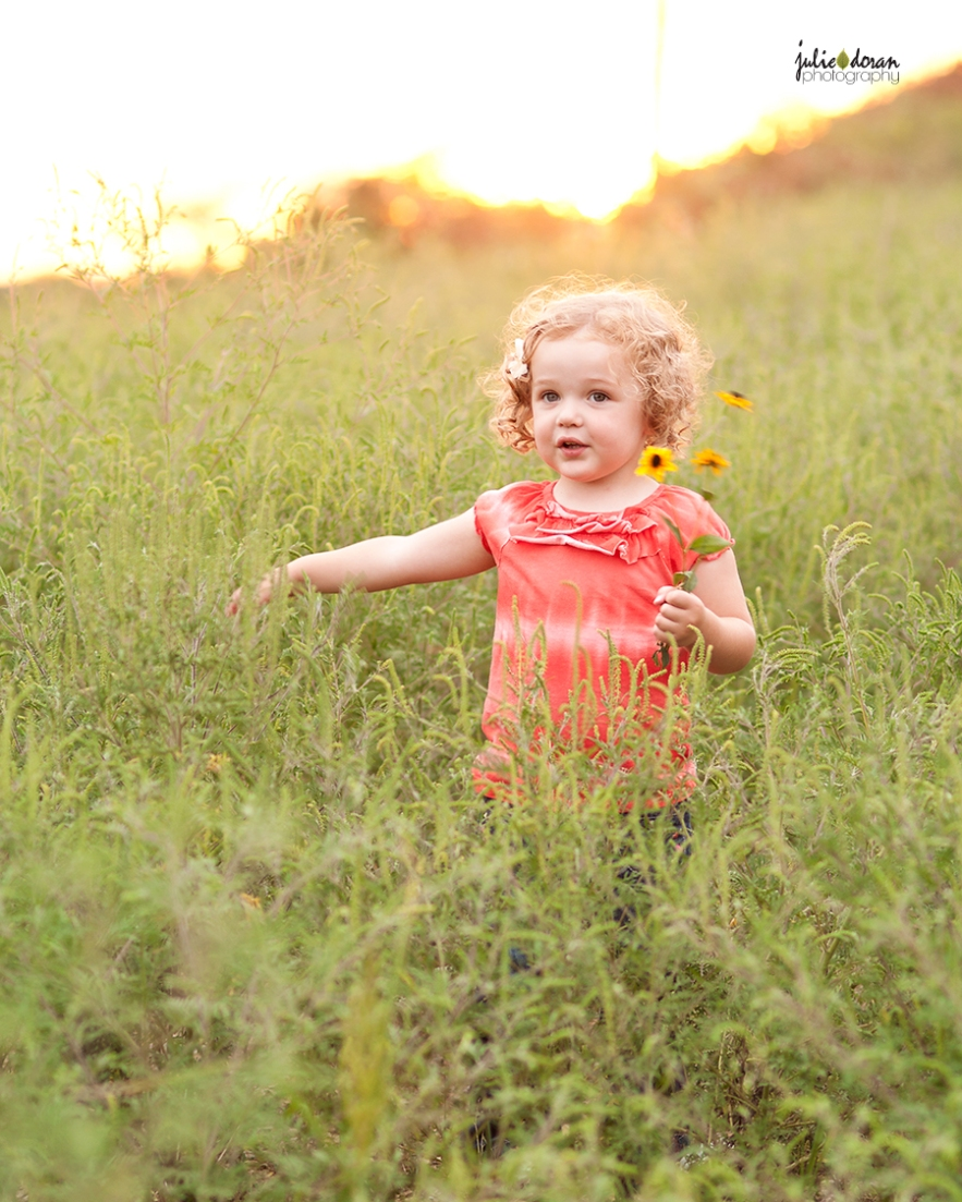 curly haired girl walking in flower field